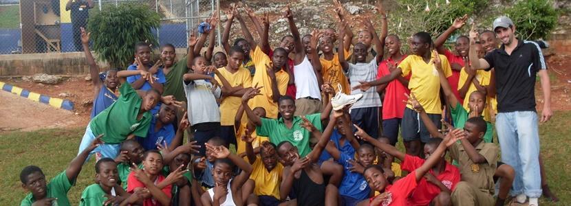 Børn og frivillige på atletikprojekt poserer
