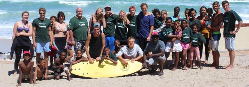 Frivillige og børn fra surfprojektet på stranden