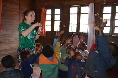 Frivillig blæser bobler for børnene som er en del af det Humanitære projekt i Madagaskar