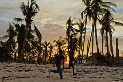 Børn løber på stranden i solnedgang