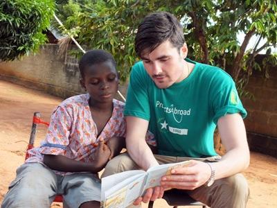 Frivillig fra England deltager i læseklub for barn i Togo