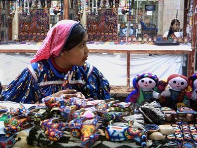 Mexicansk kvinde sælger dukker på et marked