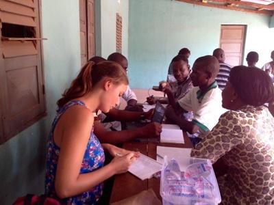 Kvindelig frivillig sidder i møde om rettighedskampagne i Togo