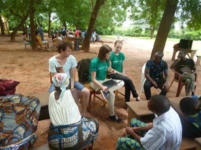 To kvindelige frivillige taler med lokale indbyggere i Togo om HIV/AIDS