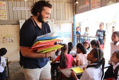 Frivillig giver materialer til skolebørn i Cambodja