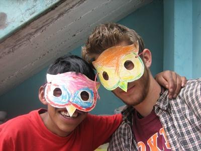 Frivillig og dreng med hjemmelavede masker