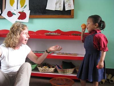 Et barn leger med en Projects Abroad frivillig på en skole i Nepal.
