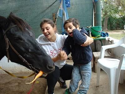 Frivillig og barn fodrer hest i Argentina