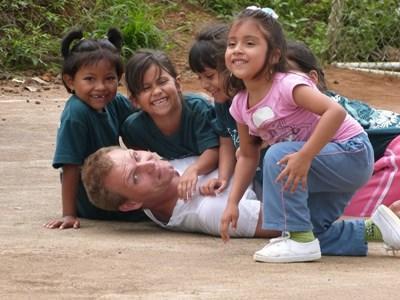 Frivillig leger med de lokale børn på humanitært projekt