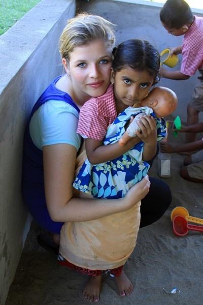 Frivillig på humanitært projekt med lille pige