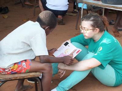 Frivillig hjælper barn med at læse på HIV-projekt