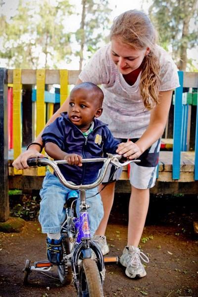 Frivillig leger med dreng på cykel