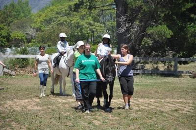 Frivillige og rytteren rider udendørs på vores hesteterapi-projekt i Sydafrika