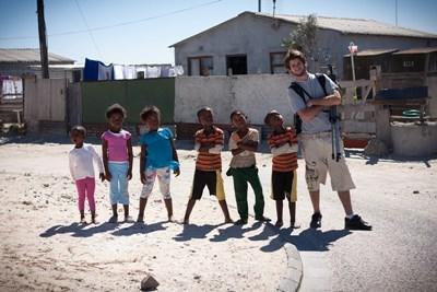 Frivillig poserer for kameraet med de lokale børn i Cape Town