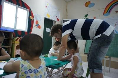 Frivillig hjælper lokale børn på humanitært projekt i Vietnam