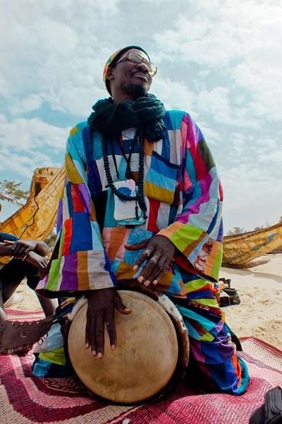 Sengalesisk mand spiller på trommer i traditionelle klæder