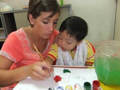 Kvindelig frivillig på ergoterapi-projekt hjælper barn med at male