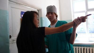 Frivillig inden for fysioterapi arbejder med kvindelig patient