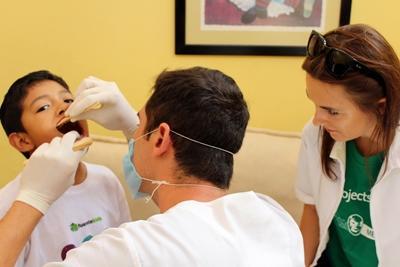Frivillig og lokal tandlæge behandler lokal dreng i Mexico