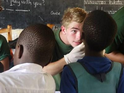 Frivillig undersøger mundhygiejne i Tanzania