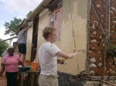 Frivillig på Påskeprojekt i Jamaica hjælper med at male et hus