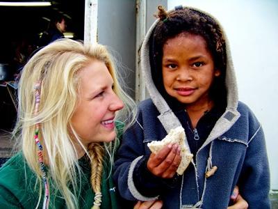 Dreng fra Cape Town og frivillig spiser en sandwich