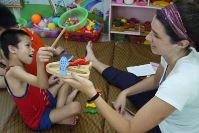 Studerende i praktik arbejder med lille handicappet dreng i Vietnam