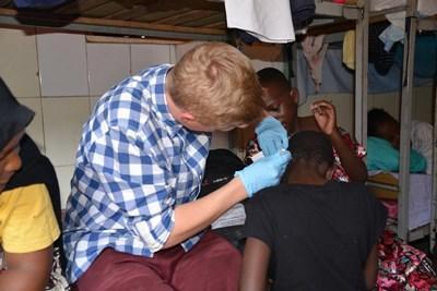 Frivillig behandler lokale børn på medicinsk projekt i Tanzania