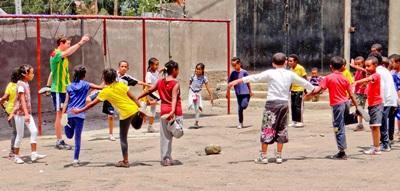 Frivillig laver strækøvelser med børn på sportsprojekt i Etiopien