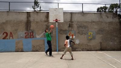 Frivillig og ung dreng spiller basketball i Addis Ababa