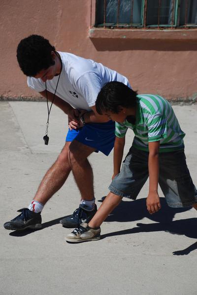 Frivillig strækker ud sammen med elev på sportsprojekt i Belize