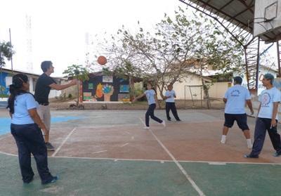 Frivillig spiller basket med lokale skoleelever