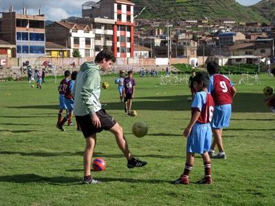 Frivillig lærer dreng nye fodboldtricks i Peru