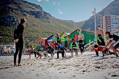 Opvarmning inden undervisning i surfing på stranden ved Muizenberg, Cape Town