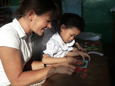 Frivillig underviser lille pige i Cambodja