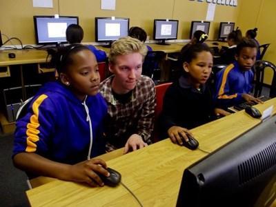 Frivillig hjælper piger på IT-undervisning i Sydafrika