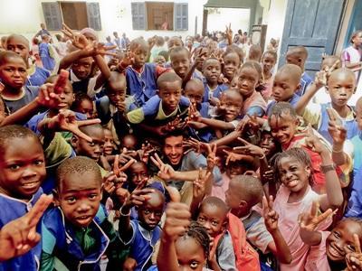 Frivillig omringet af skolebørn i Senegal