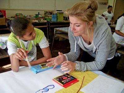 Frivillig på undervisningsprojekt i samtale med elev
