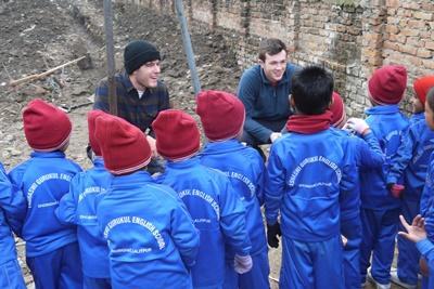 To mandlige frivillige fra Projects Abroad taler med skolebørn ved deres nye bygning