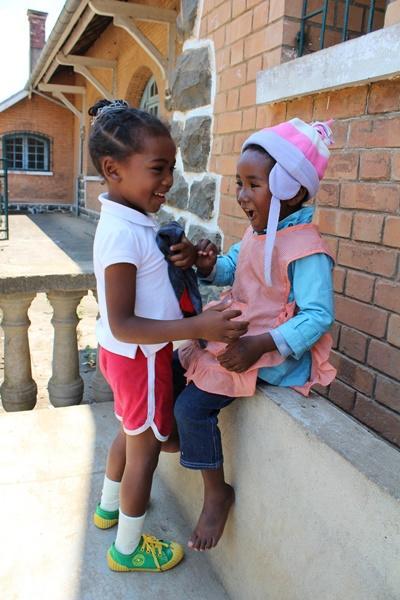 To små piger leger uden for deres hus i Madagaskar