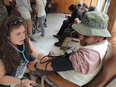 Frivillig på ungdomsprojekt måler blodtryk på bolivianer